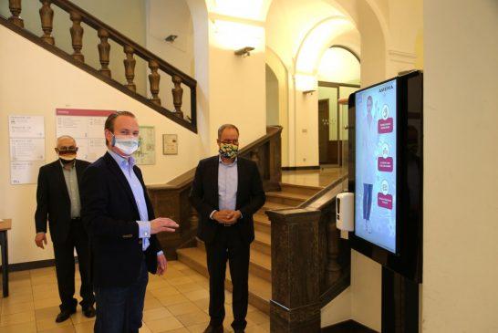 Corona-Prophylaxe-Station in Heidelberg: gestengesteuerter Bildschirm und Desinfektionsmittel-Spender